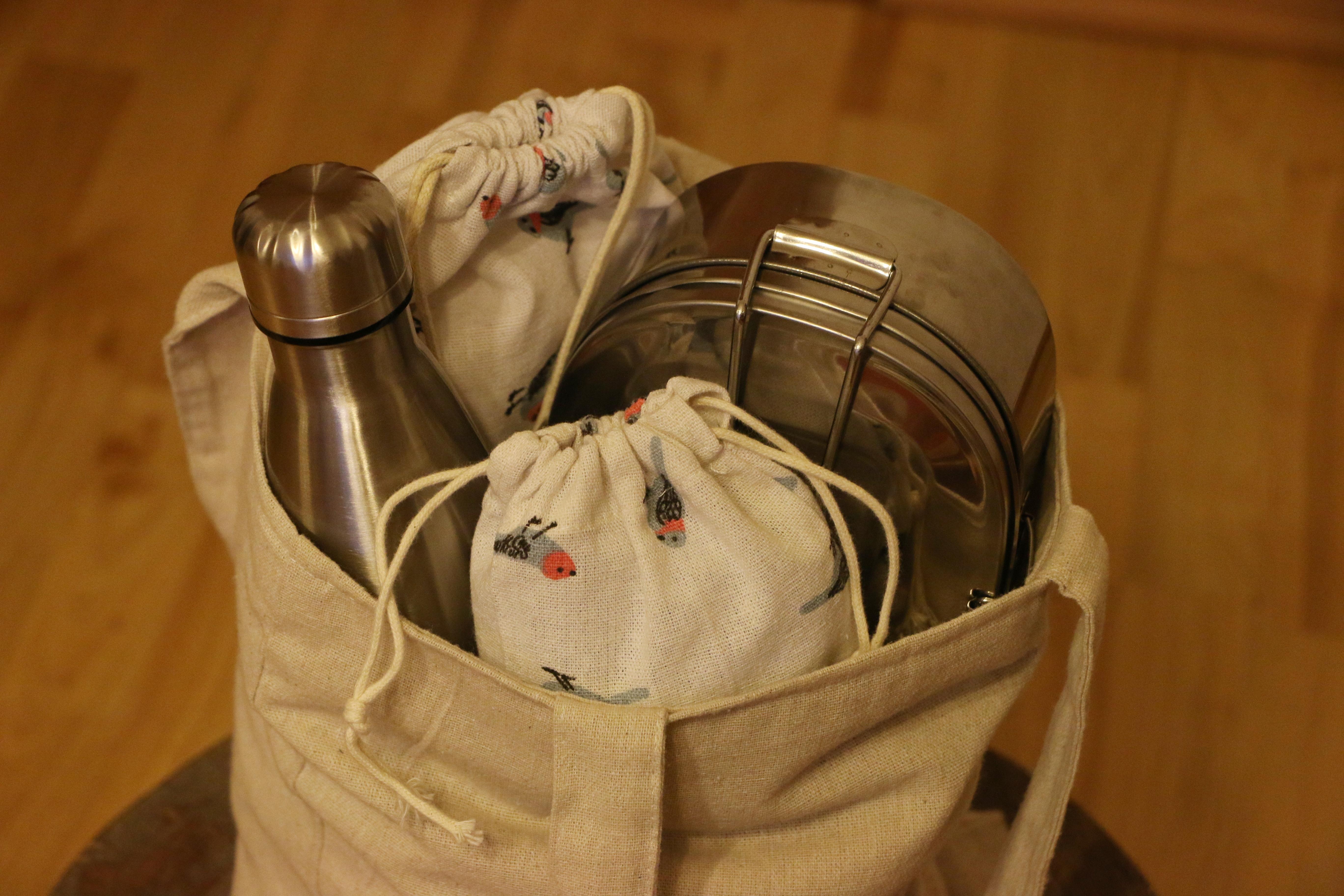 Taška plná zero waste produktů - nerezové lahve, látkové pytlíky, nerezová krabička